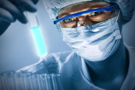 medicina: Cient�fico enmascarada en vasos de estudiar una muestra luminosa Foto de archivo