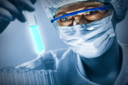 medicine: Masked female scientist in glasses studying a luminous sample