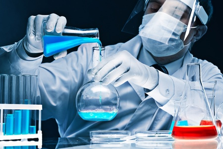 glassware: Masked male scientist mixing bright blue substances in glassware