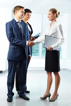 shake hands: Vertical full-length shot of business people shaking hands with a smile Stock Photo