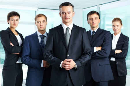 ceo: Group portrait of a professional business team looking confidently at camera