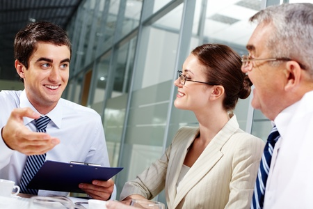 Three business partners sitting in office and interacting at meeting Stock Photo - 12620268