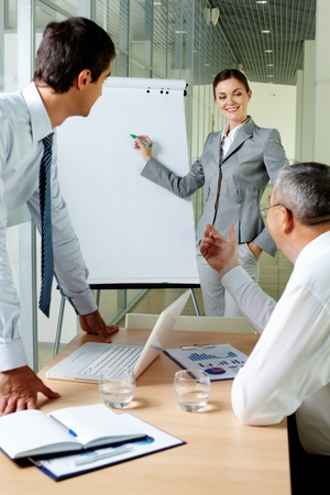 Young businesswoman explaining her ideas on whiteboard at meeting photo