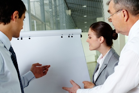 Three business partners pointing and looking at whiteboard at meeting photo