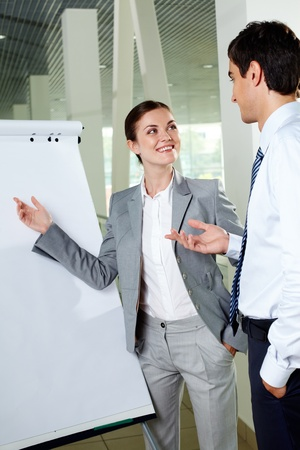 Two young associates by whiteboard looking at one another while communicating photo