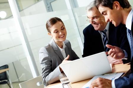 Succesvolle businessteam van drie zitten in kantoor-en planning van het werk