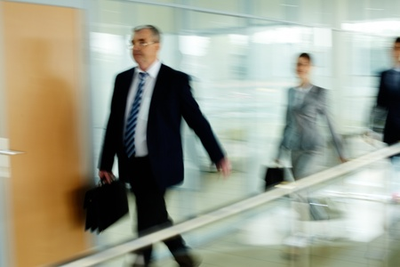 Businessman going along corridor with walking people on background photo