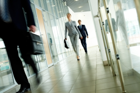 go inside: Businesspeople going along corridor inside office building Stock Photo