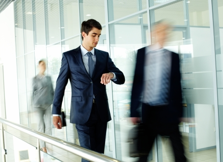 office environment: Businessman looking at watch with walking people on background