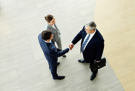 Image of business partners handshaking after striking deal with smart woman near by photo