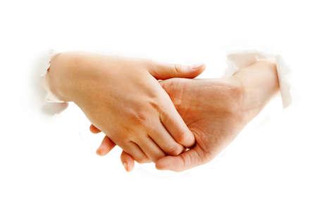 manos unidas: Foto del apretón de manos a través de papel rasgado