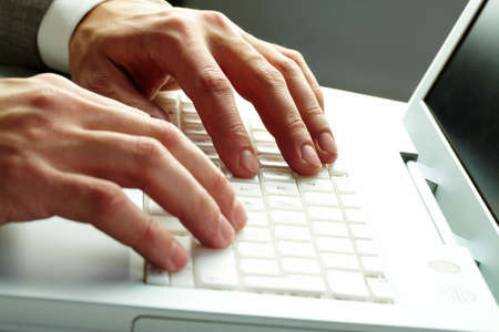 Close-up of male hands over white keyboard of laptop during typing photo