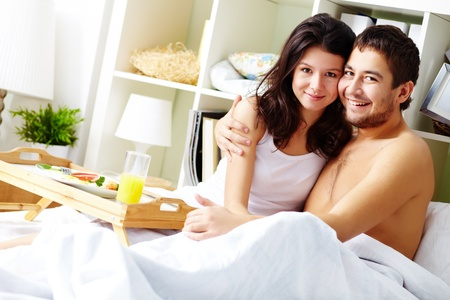 A young man embracing his girlfriend while sitting in bed in the morning Stock Photo - 12620200