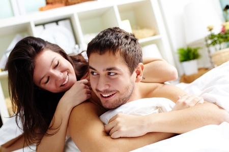 enamorados en la cama: Feliz pareja joven tumbado en la cama