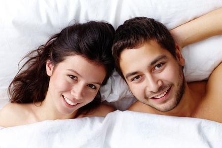 romance bed: Happy young couple lying in bed and looking at camera