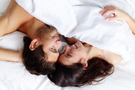 pareja en la cama: Feliz pareja joven tumbado en la cama y mirando el uno al otro