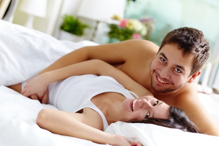 Happy young couple lying in bed and looking at camera with smiles Stock Photo - 12620198