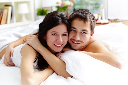 Happy young couple lying in bed and looking at camera Stock Photo - 12620203