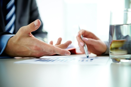 reviews: Image of male hand pointing at business document during discussion at meeting Stock Photo
