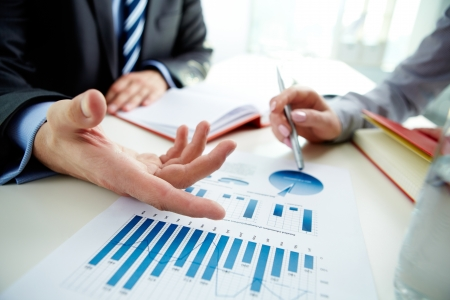 Image of male hand pointing at business document during discussion at meeting Stock Photo