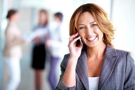 persona llamando: Imagen de la empresaria muy llamando por teléfono en el entorno de trabajo Foto de archivo