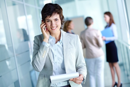 Image of busy female calling on the phone and looking at camera in working environment Stock Photo - 12620205