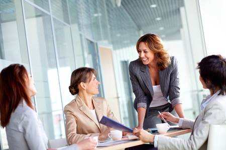 people communicating: Image of four successful businesswomen interacting at meeting