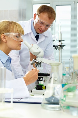 pharmaceutical bottle: Pretty clinician studying new substance in microscope with her colleague near by