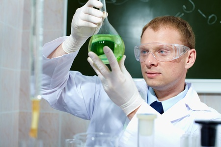clinician: Serious clinician looking at flask with green liquid in laboratory Stock Photo