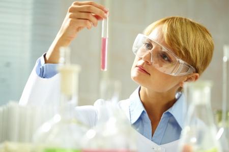 investigador cientifico: Un joven qu�mico mirando pensativamente a la tuber�a con el l�quido Foto de archivo