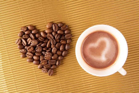 Photo of cup of coffee with shape of heart made up of beans near by photo