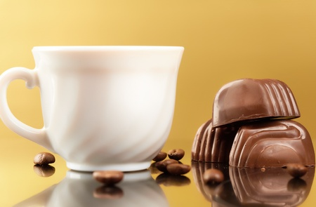 Photo of porcelain coffee cup with coffee beans and chocolates near by photo
