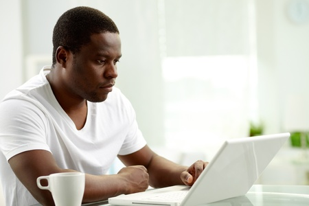 Image of young African man typing on laptop at home Stock Photo - 12872819