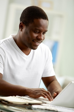 Image of young African man typing on laptop at home photo