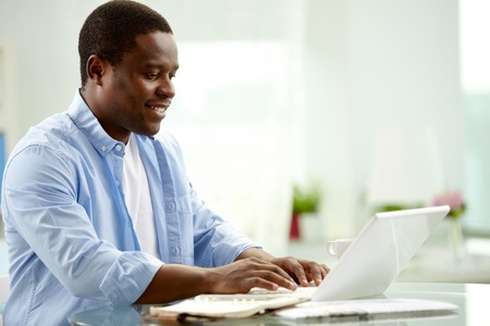 Image of young African man typing on laptop Stock Photo - 12873243