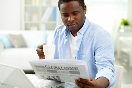 Image of young African man reading news in the morning photo