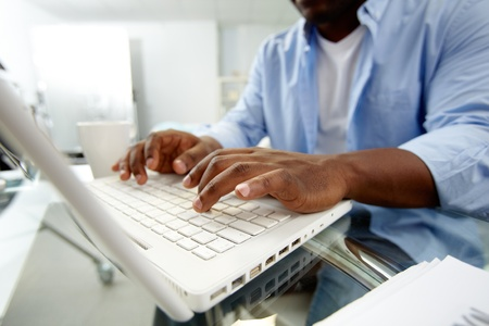 Close-up of African man typing on laptop Stock Photo - 12873292