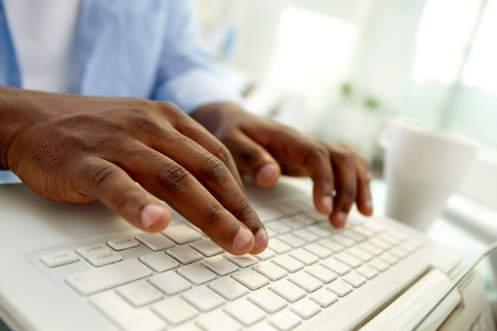 african education: Close-up of African man typing on laptop Stock Photo