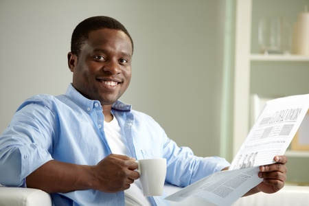 Image of young African man with newspaper looking at camera Stock Photo - 12872804