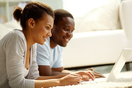 Image of young African couple networking at home photo