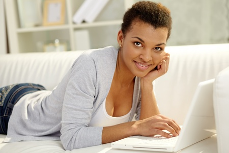 Image of young African girl looking at camera while typing Stock Photo - 12873290