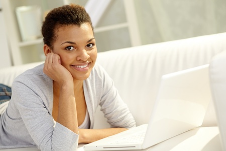 Image of young African girl looking at camera with laptop near by Stock Photo - 12873275