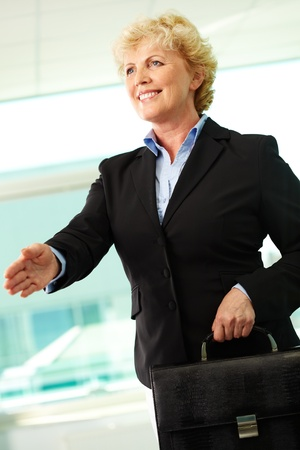 middle age women: Portrait of smiling middle aged businesswoman with briefcase giving her hand for a handshake