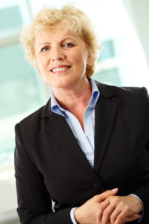 Portrait of smiling middle aged businesswoman looking at camera photo