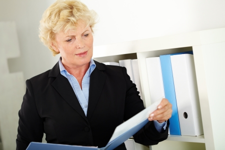 aged business: Portrait of middle aged businesswoman reading paper in office Stock Photo