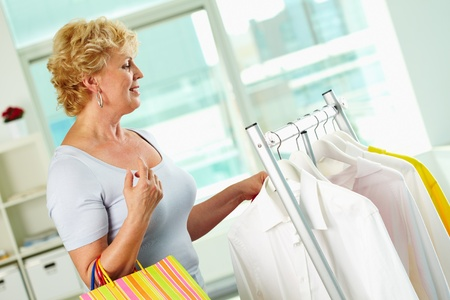 Portrait of middle aged woman with paperbags in clothing department photo