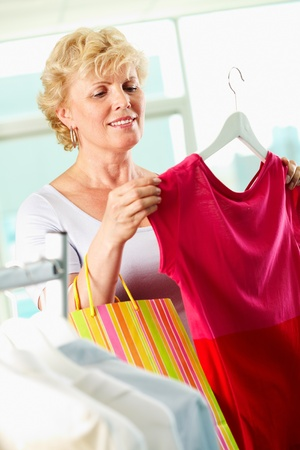 Portrait of middle aged woman choosing new tanktop in clothing department Stock Photo - 12872812