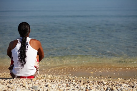 Young man sitting on the beach enjoying peaceful moment photo