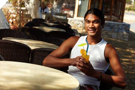 young fellow: Young Latino man with cocktail during vacation on resort