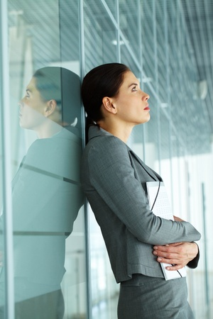 mujer pensativa: Pensativo de negocios con los documentos por la pared Foto de archivo